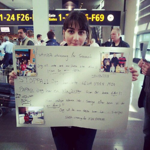 """Siavash's daughter Jasmine with a sign explaining her pain. """"Stop!! Stop!!! I cannot live without my dad!"""""""