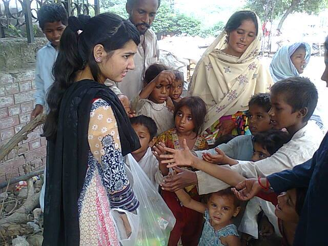 En kristen kvinna i Pakistan delar ut matpaket efter en natrkatastrof